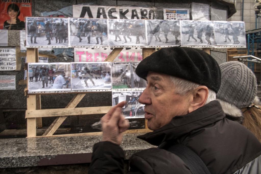 Des passants commantent les photographies exposees des affrontements.